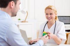 采取健康保险卡片的年轻可爱的医生 免版税图库摄影