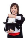 采取兔子的年轻魔术师男孩在他的帽子外面 库存图片