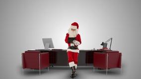 采取关于一张剪贴板的圣诞老人笔记在他的现代圣诞节办公室,反对白色,储蓄英尺长度 股票录像