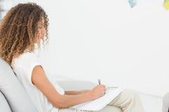 采取关于剪贴板的治疗师笔记坐长沙发 免版税图库摄影