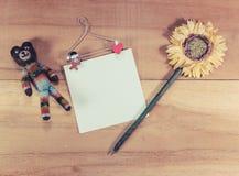 采取关于木地板的笔记的熊和笔 库存照片