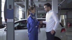 采取关于汽车检查的和友好的女性汽车专家数据与一个客户握手汽车的 影视素材