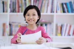 采取关于纸的逗人喜爱的女小学生笔记 库存照片