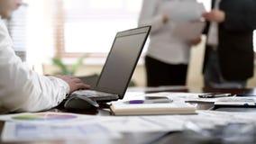 采取关于膝上型计算机的工作者笔记,当两个同事谈论纸在办公室时 库存图片