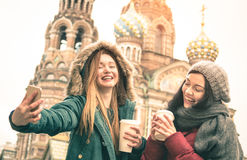采取冬天selfie的愉快的女朋友在圣彼得堡 免版税图库摄影