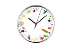 采取准时疗程的概念 有由各种各样药片、胶囊,片剂和医药做的拨号盘的模式时钟 库存照片