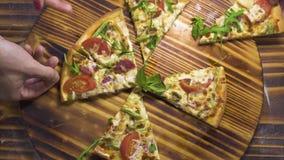 采取切片从木台式视图的人手热的比萨 在木桌背景比萨店的新鲜的切的比萨 影视素材