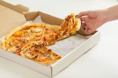 采取切片新鲜的薄饼的手 卡路里食物 免版税图库摄影