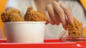 采取卡路里酥脆鼓槌的,不健康的便当快餐的女性手富有 影视素材