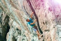 采取危险的行动的成熟男性登山人在岩石太阳发光 免版税库存图片