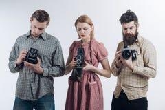 采取另一射击 无固定职业的摄影师或摄影记者有葡萄酒老照相机的 减速火箭的样式妇女和人拿着模式照片 免版税库存图片