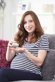 采取叶酸片剂的孕妇 免版税库存照片