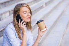 采取咖啡休息和使用智能手机的女实业家 免版税库存照片