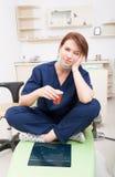 采取咖啡休息的疲乏的女性牙医医生 免版税库存图片