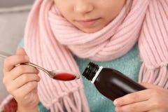 采取咳嗽糖浆的小女孩 免版税库存照片
