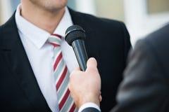 采取商人的采访新闻工作者 免版税图库摄影