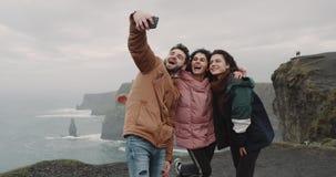 采取图片在有美好的风景的令人惊讶的地方与大峭壁的特写镜头愉快的朋友,他们微笑大 股票录像