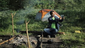 采取图片在片剂的一个人火 反对背景清早是一个帐篷在森林里 股票录像