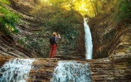 采取图片在他的手机的男性旅客瀑布 Gelendzhik,北高加索,俄罗斯 图库摄影