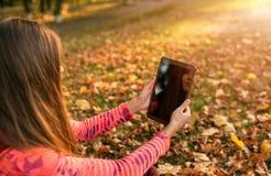 采取图片数字式片剂个人计算机的女孩在秋天公园 免版税库存图片