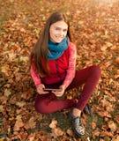 采取图片数字式片剂个人计算机的女孩在秋天公园 库存照片