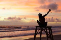 采取在一个救生员塔的剪影妇女一selfie在与太阳上升和绘天空的阳光的一个海滩 库存照片