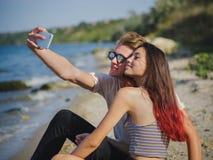采取在一个河岸的一个美丽的女孩和家伙的特写镜头一selfie在自然被弄脏的背景 库存照片