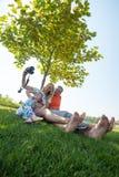 采取在一个绿色草甸的快乐的家庭selfie 库存照片