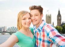 采取在伦敦市的愉快的夫妇selfie 库存照片