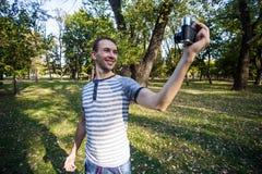 采取在减速火箭的照相机的年轻人selfie 免版税图库摄影