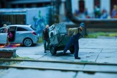 采取在台车的两名工作者一台老洗衣机 免版税库存图片