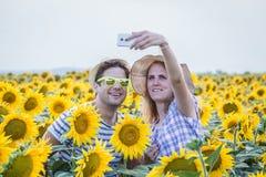 采取在向日葵领域的年轻夫妇自画象 库存照片
