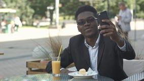 采取在咖啡馆的愉快的非裔美国人的商人selfie 库存图片