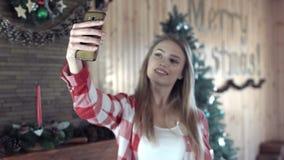 采取在圣诞树前面的妇女selfie 影视素材