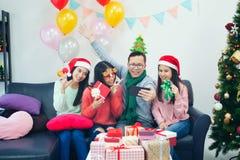 采取在圣诞老人帽子的小组不同种族的工友selfie在o 库存照片