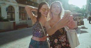 采取在城市街道上的两个年轻美丽的女孩selfie 股票录像