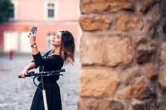 采取在城市街道上的可爱的妇女selfie 做面孔的少妇画象在照相机 库存图片