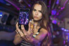 采取在大型高级轿车的年轻女性一selfie 免版税库存图片