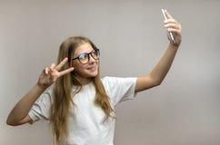 采取在她的智能手机的一selfie一个白肤金发的女孩的画象 r 年轻博客作者 免版税库存照片