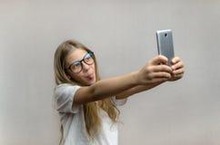 采取在她的智能手机的一selfie一个白肤金发的女孩的画象 r 年轻博客作者 图库摄影