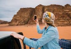 采取在她的智能手机的妇女selfies她的假期在瓦地伦沙漠 免版税库存图片