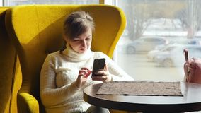 采取在她的智能手机的美女一selfie,当坐在咖啡馆时 企业咖啡杯方便问题午餐开张了 慢的行动 影视素材