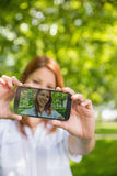 采取在她的电话的俏丽的红头发人一selfie在公园 免版税库存照片