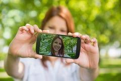 采取在她的电话的俏丽的红头发人一selfie在公园 免版税库存图片