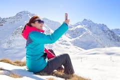 采取在她的电话的年轻女性一selfie在美好的山上面 花雪时间冬天 免版税库存图片