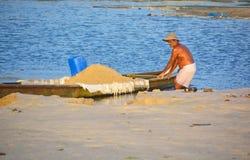 采取在小船的人沙子 库存照片