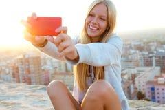 采取在屋顶的美丽的白肤金发的女孩一selfie 免版税库存照片