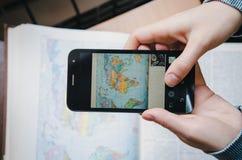 采取在屏幕黑色的学生少妇一本照片世界地图图象书与智能手机 顶视图 女性现有量藏品 免版税图库摄影