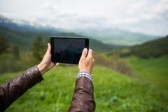 采取在山的年轻人片剂selfie 免版税库存图片