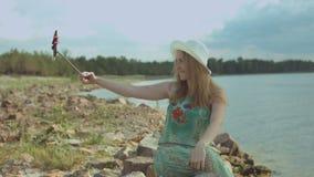 采取在巧妙的电话的快乐的妇女selfie在海滩 影视素材